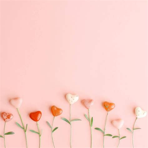 Candy hearts on stems against pink background - by